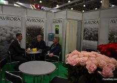 Alexander Grismen from Avrora having a conversation with two clients.