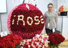 Nany Santin of Floricola Irose standing next to a beautiful piece of rose art.