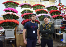 Two vendors standing in front of their Ecuadorian roses.