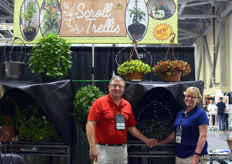 """Larry and Diane McMurray of Scroll Trellis. In the back the new ""All-in-One Hanger and Trellis"" for hanging baskets and the second is called the ""Latch-on-Pot Trellis"" for patio pots. For more information on this trellis, see: www.floraldaily.com/article/16235/US-New-trellis-adds- value-night-and-day."""